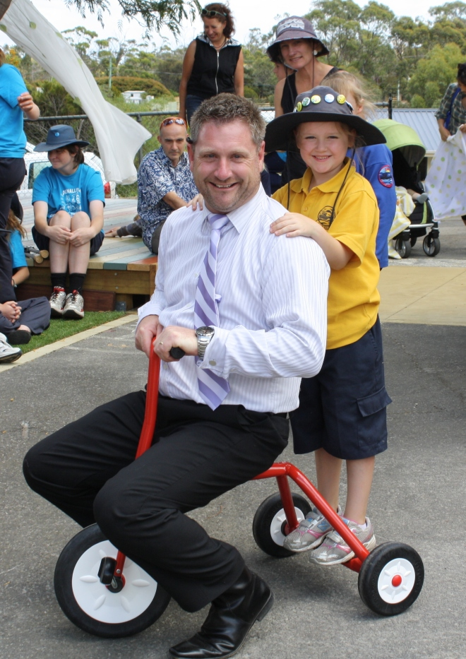 Principal Matt Kenny with his  red tricycle in the new kinder playground.